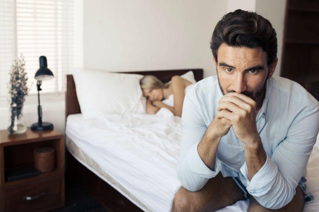 Tristezza post orgasmo: nell'immagine un uomo seduto sul letto con aria malinconica. La sua partner lo osserva in secondo piano, sotto le lenzuola
