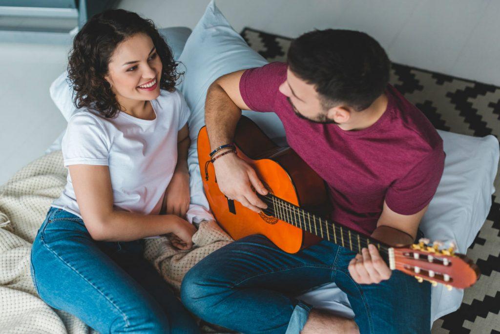 Musica per fare l'amore: una coppia sul letto. Lui suona la chitarra
