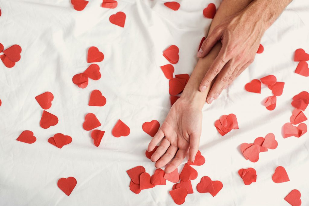 Cose da non fare durante il rapporto sessuale: nell'immagine si vede una mano maschile appoggiata su di una mano femminile su di un letto cosparso di cuori rossi di carta.