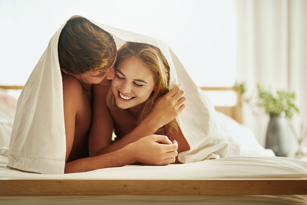 Sex toys - giocattoli erotici: una coppia sorride sotto le lenzuola