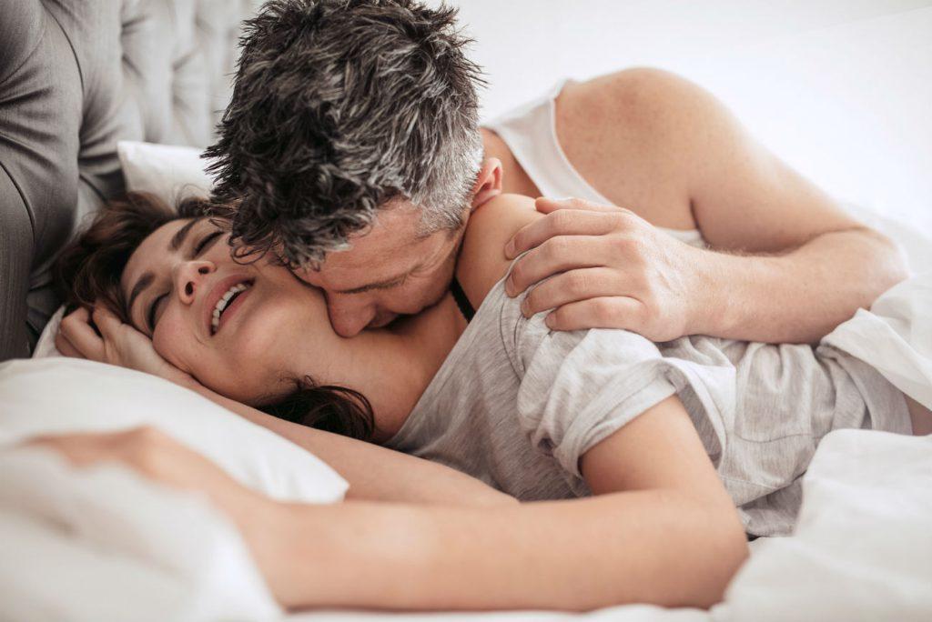 Capire gli uomini: 5 cose che lui non nota durante il sesso - nellìimmagine un uomo bacia sul collo una donna a letto