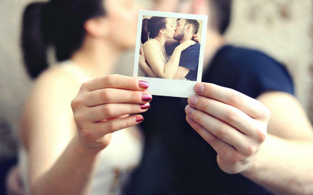 Giornata Mondiale del Bacio: una coppia si bacia tenedo in mano una polaroid che ritrae il bacio