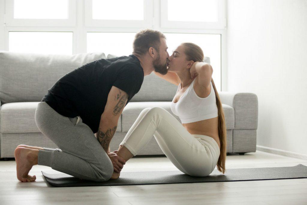Quante calorie si bruciano facendo l'amore? Nell'immagine una coppia fa fitness in casa e si bacia