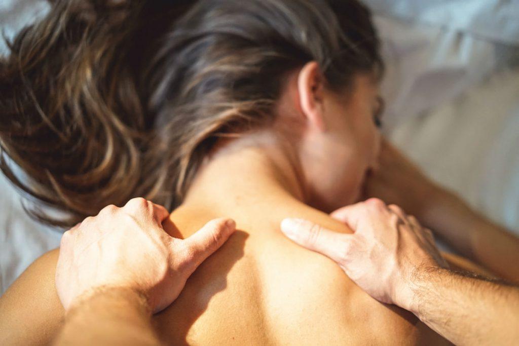 Un uomo esegue un massaggio sensuale alla propria partner